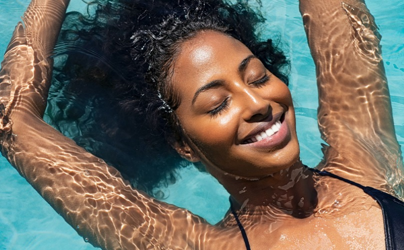 lifestyle image of a woman sunbathing in the pool