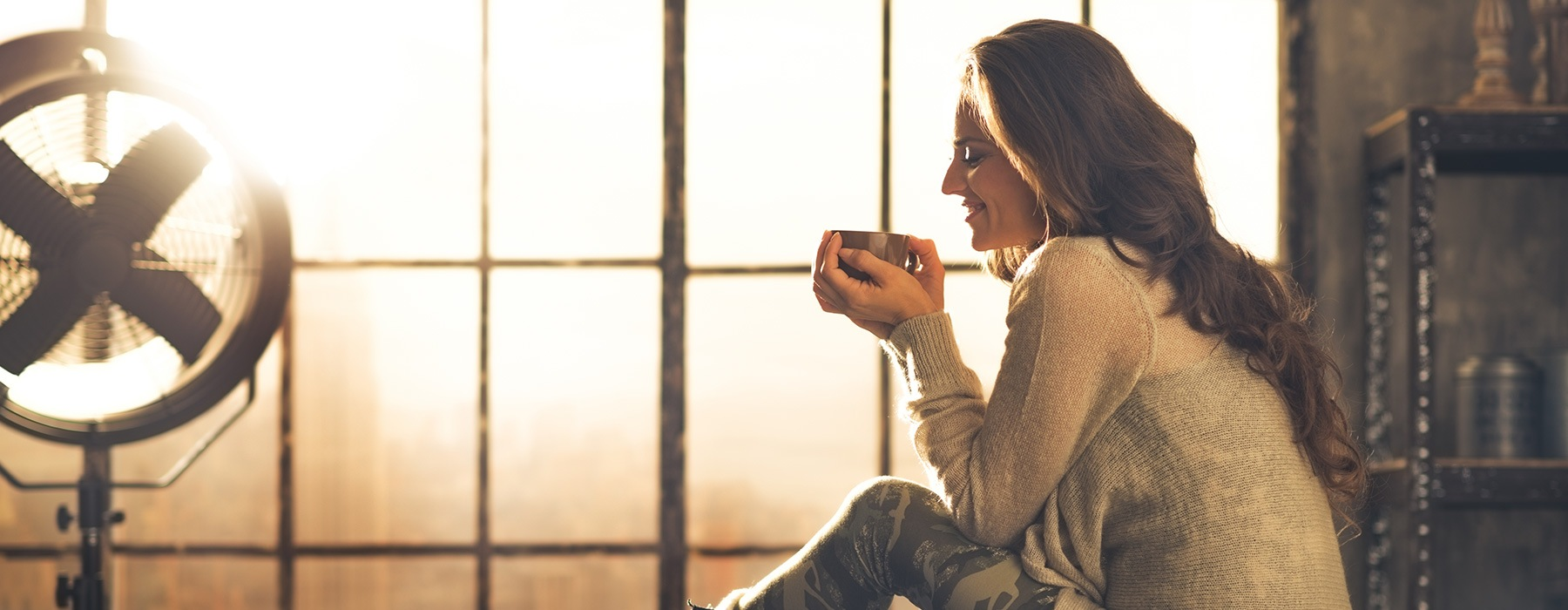 lifestyle image of a woman holding a cup of coffee beside a large window