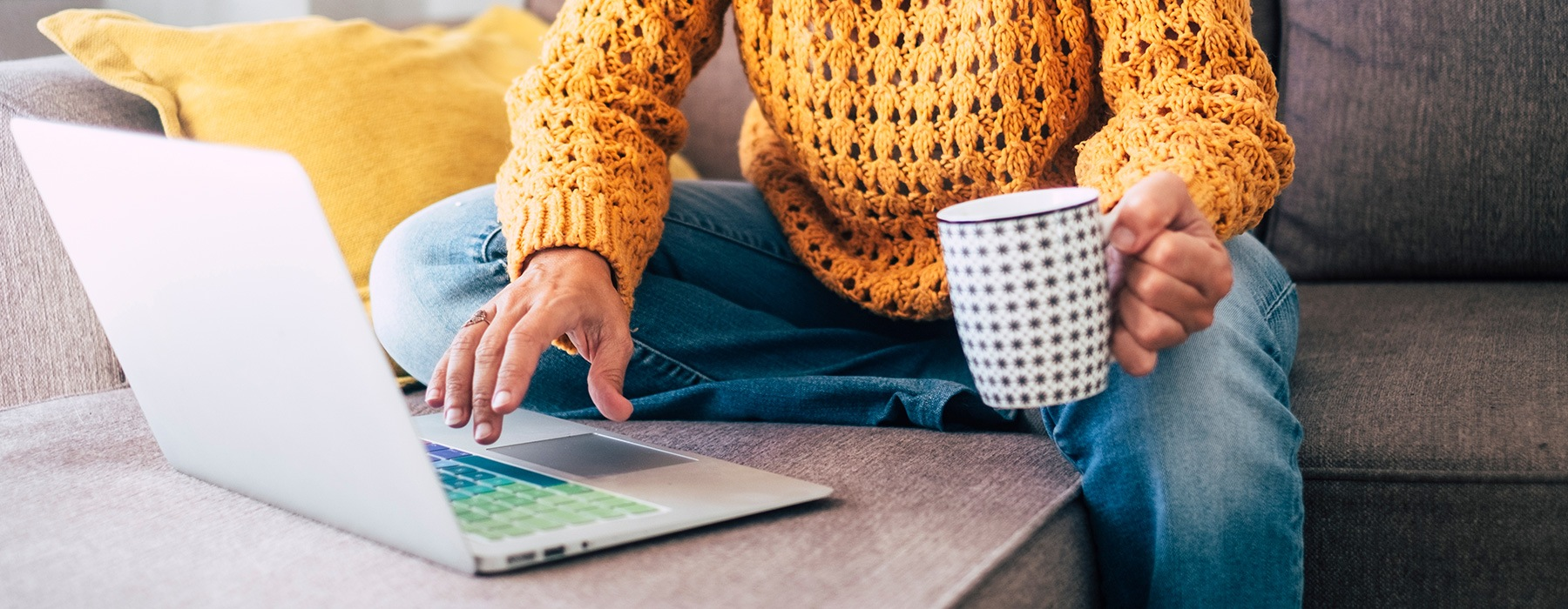 lifestyle image of a person holding a mug while working on a laptop